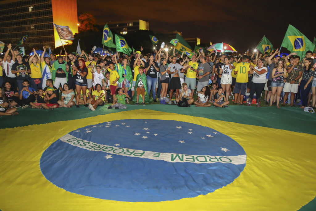 Supporters of far-right presidential candidate Jair Bolsonaro, celebrate in front of the National Congress in Brasilia, after the former army captain won Brazil's presidential election, according to official results that gave him 55.7 percent of the vote, on October 28, 2018. - Far-right former army captain Jair Bolsonaro was elected president of Brazil on Sunday, beating leftist opponent Fernando Haddad in a runoff election after a bitter and polarized campaign. Official results gave the controversial president-elect 55.18 percent of the vote with more than 99.7 percent of the ballots counted. (Photo by Sergio LIMA / AFP)