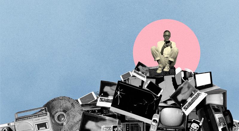 Una mujer con su celular encima de una montaña de electrodomésticos desechados.
