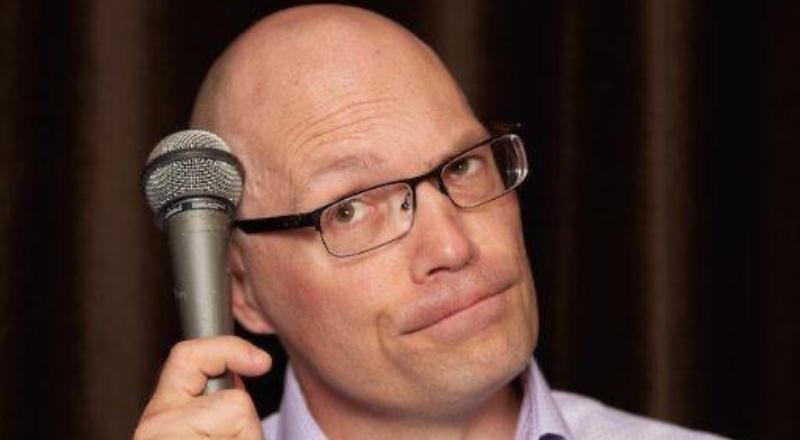 Hombre con lentes hace muecas y sostiene un micrófono junto a su cabeza.