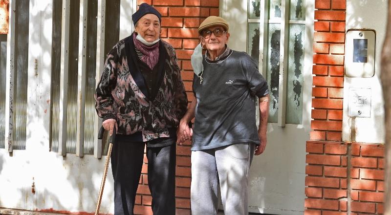 Una mujer y u hombre mayor posan en la puerta de una casa, parados de frente a la cámara.