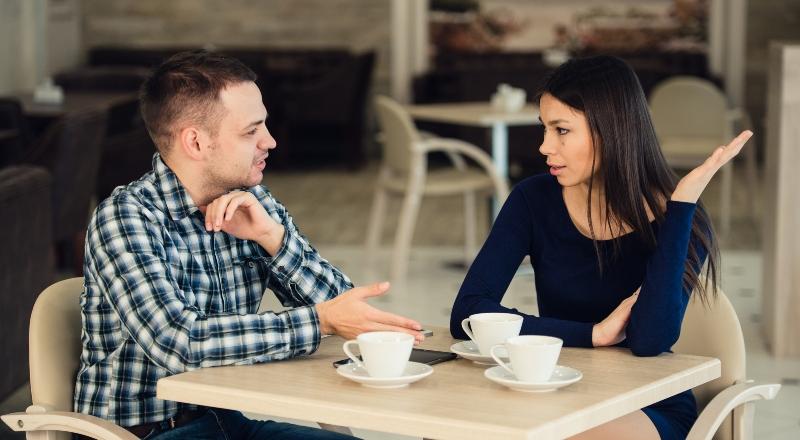 Una pareja joven discute senada en la mesa de una confitería.