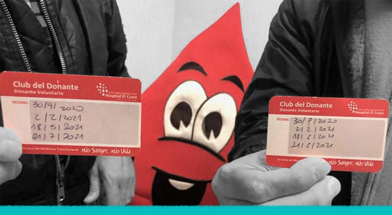 Dos manos sostienen sus carnets con las fechas de donación de sangre.